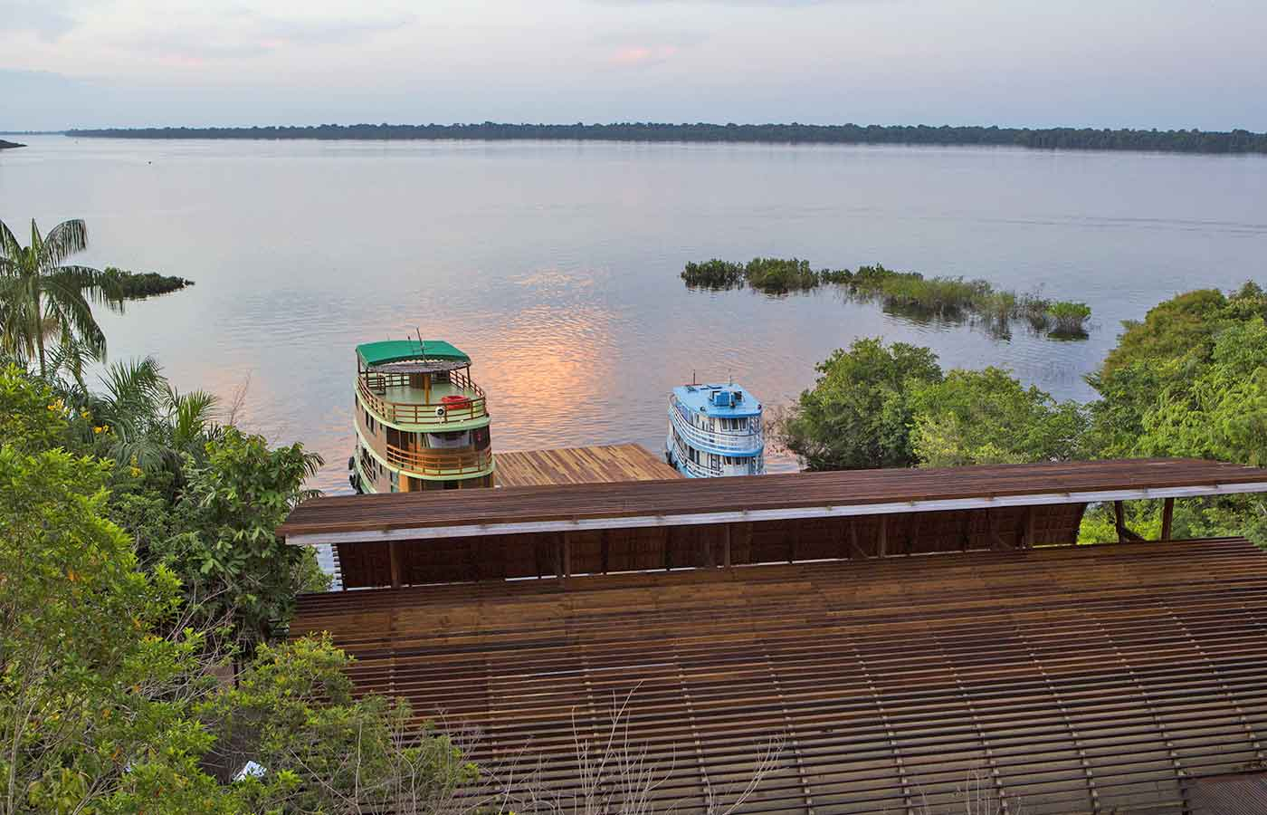 A dusk view of Negro river with regional boats from Mirante-do-Gaviao in Amazonas, Brazil