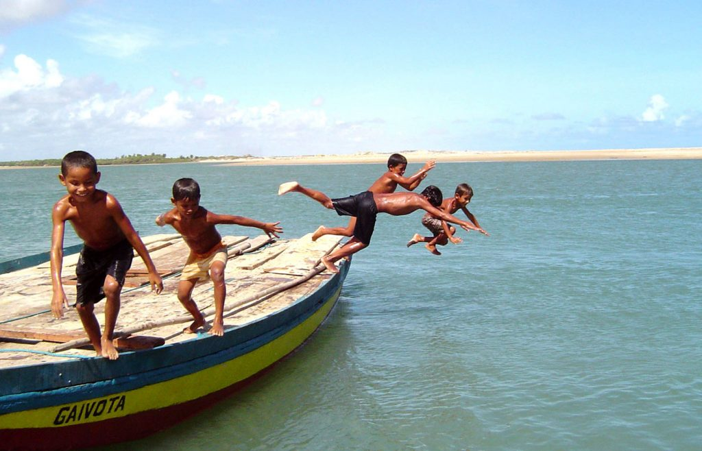 Local children playing on a boat in Jericoacoara