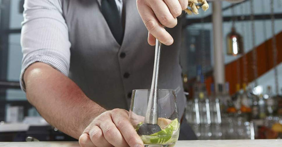 A bartender prepares a traditional caipirinha drink